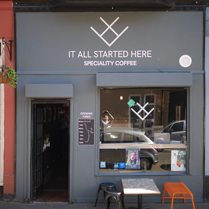 The minimalist grey facade of It All Started Here coffee shop. There is a door leading inside to the left and a large picture window to the right of it.
