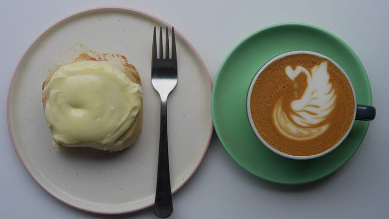 A cake with white icing on a white plate with a fork sits next to a green saucer with a cup of coffee with latte art of a leaf.