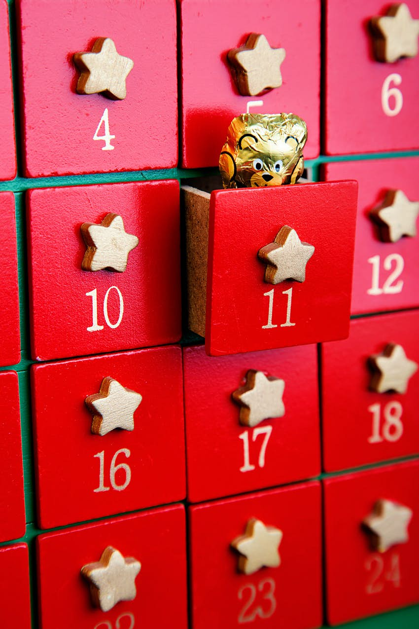 An advent calendar with red wooden drawers featuring gold stars. The eleventh drawer is slightly open to reveal a teddy-shaped chocolate wrapped in gold foil.