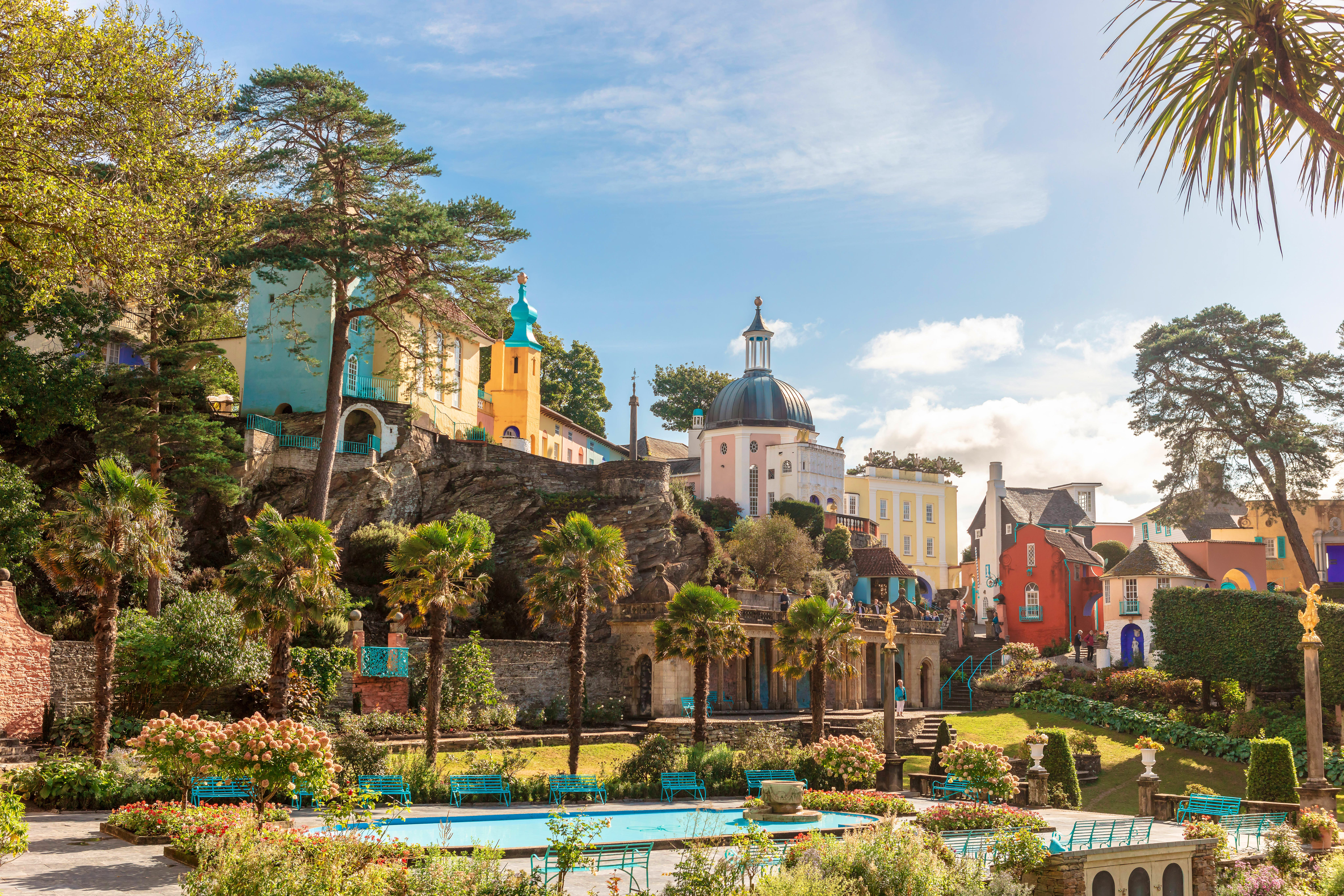 A park in Portmeirion; it has been planted with Mediterranean-style trees and plants, and it's surrounded by several elevated, brightly coloured buildings, giving the impression of an Italian hilltop town.