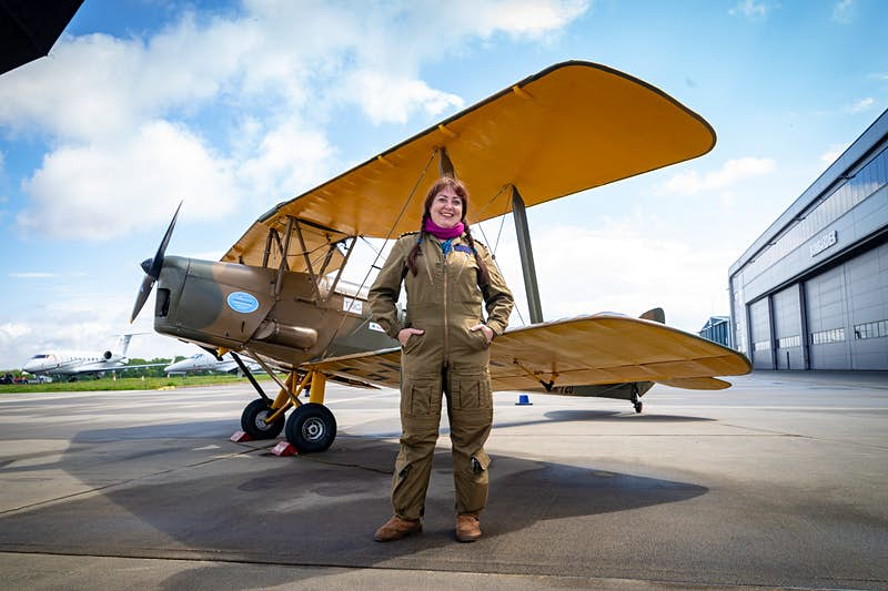 A female pilot in a flight suit stands beside her Tiger Moth plane at an airfield