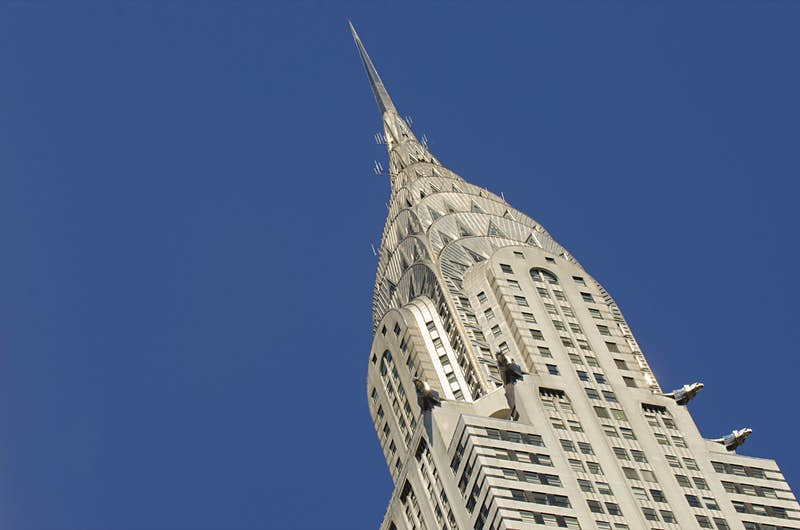 The silver-gray top of the Chrysler Building is framed at an angle against a blue sky; Best American architecture