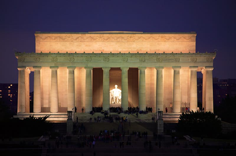 The statue of Abraham Lincoln is illuminated inside the Lincoln Memorial temple at night; Best American architecture