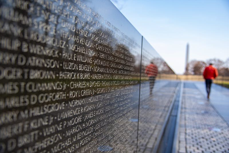 A man in a red coat is reflected in the black granite walls of the Vietnam Veterans Memorial as he walks toward the Washington Monument on a cold day. The names of deceased veterans are etched in the wall over his reflection; Best American architecture