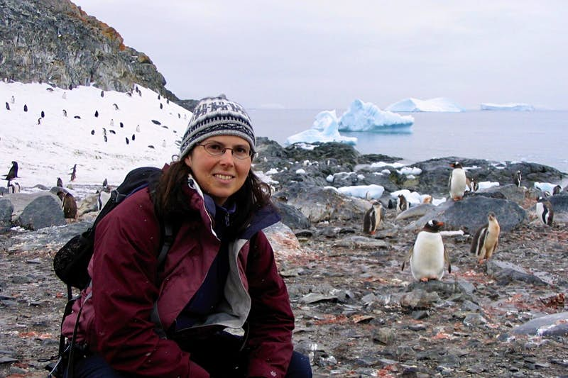 Marie-France poses next to some penguins near the coastline in Antarctica