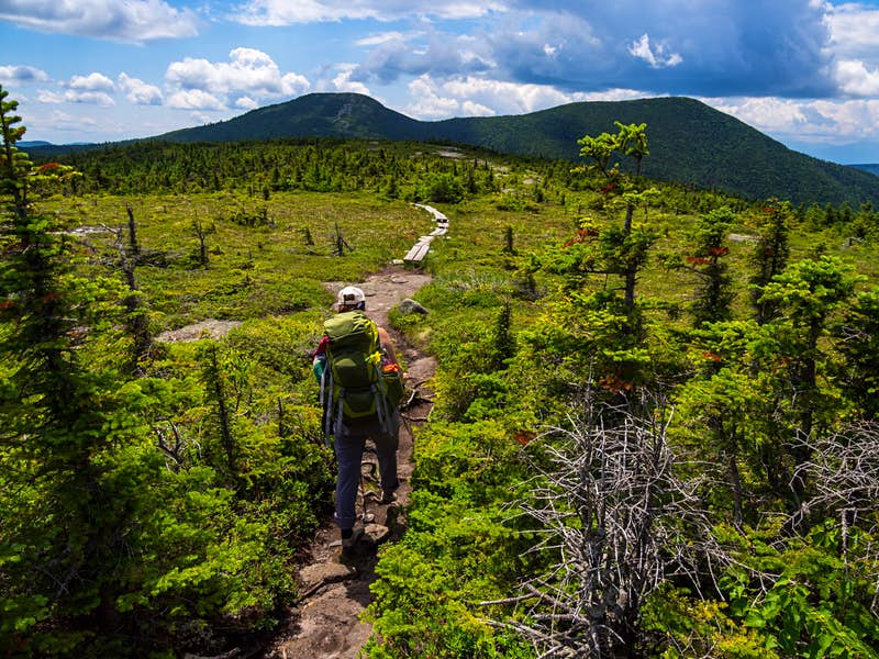 Hiker on the Appalachian Trail in Maine with Lush Mountain.