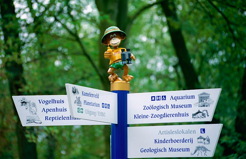 A statue of a monkey wearing shorts, a t-shirt and hat, holding binoculars and giving a thumbs-up stands on top of a sign at a zoo
