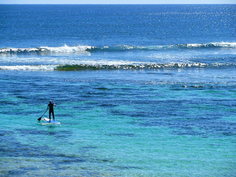 View of the back of a man in the distance, standing on a paddle board, paddling out alone into the ocean towards the waves; places for stand up paddle boarding