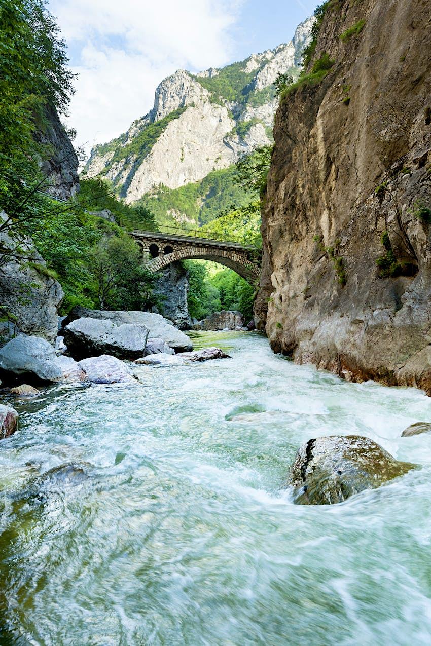A stone bridge spans a churning river in Rugova Gorge