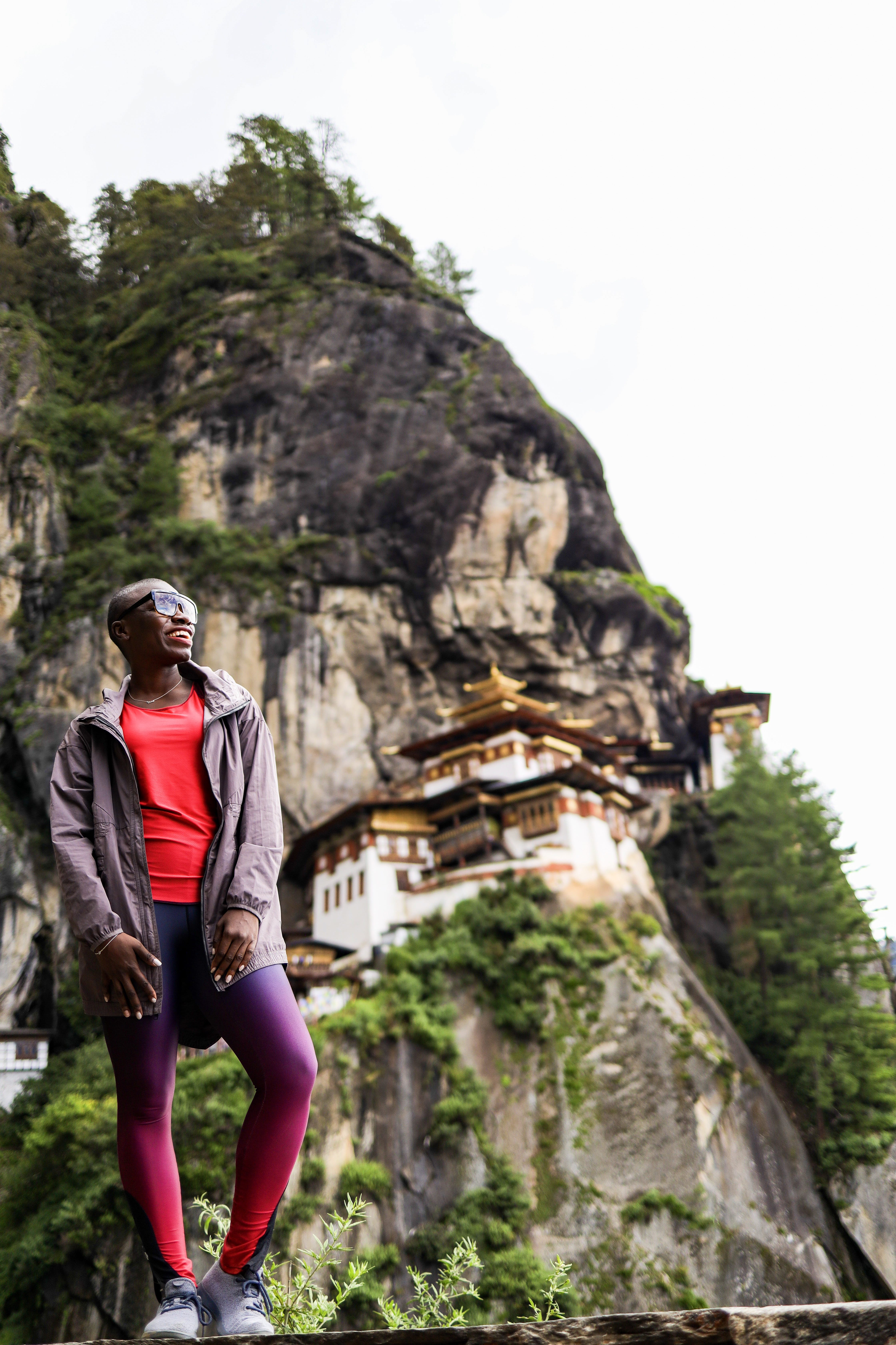 Jessica smiling looking away from the camera standing in front of a large house embedded in the side of a mountain in Bhutan