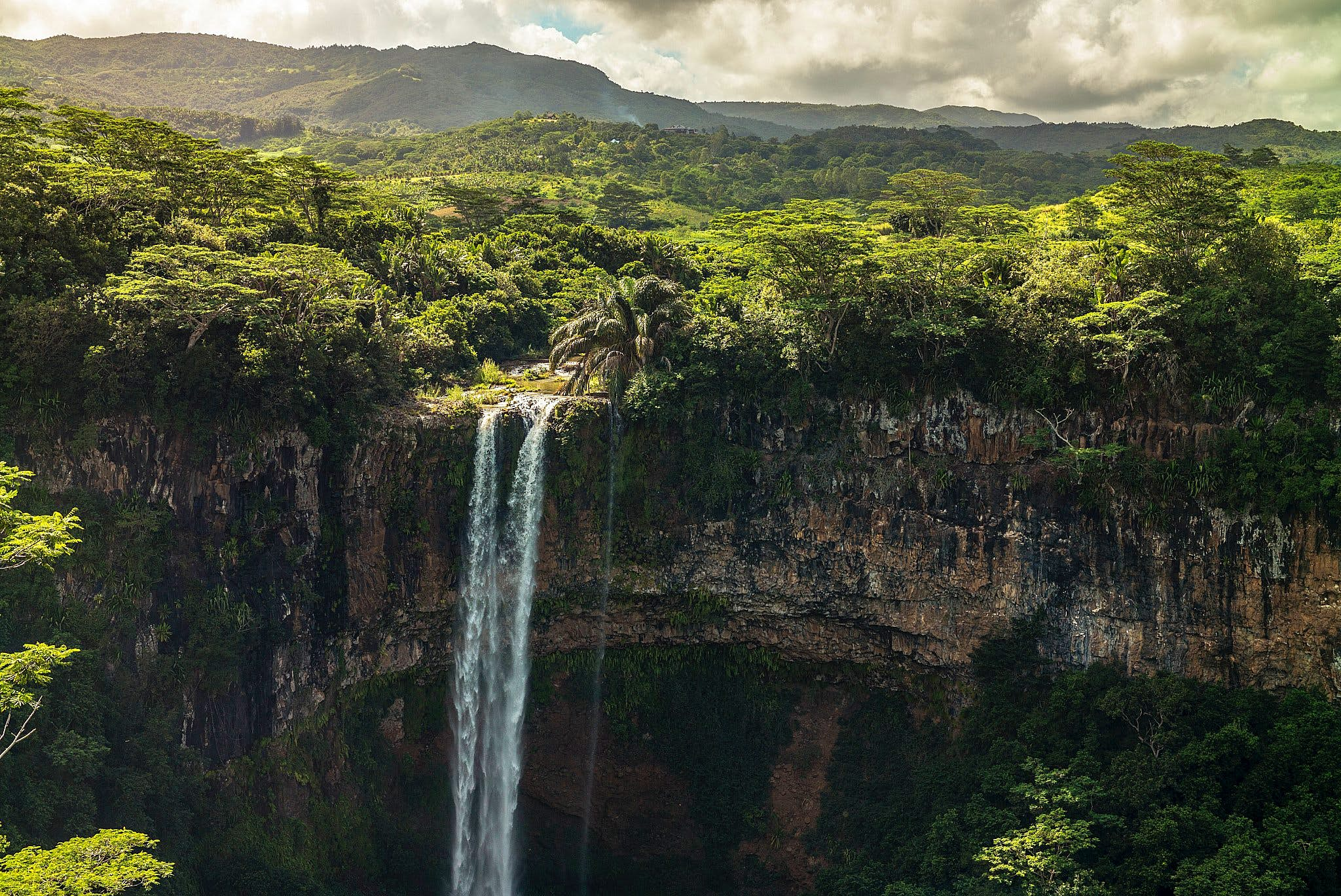 A waterfall cascades over a cliff face in front of verdant forest near Chamarel, Mauritius.