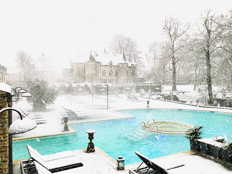 A bright blue pool with a round hot tub in the center is surrounded by snow, with a classic Belgian chalet in the background, its roof and turrets slightly obscured by fresh falling snow