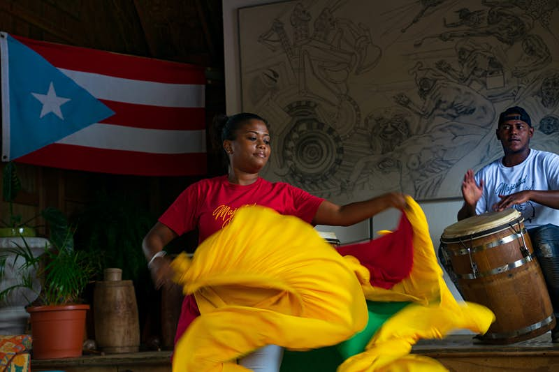 A woman twirls her brightly colored skirt at a man plays a drum in the background; Sustainable Puerto Rico