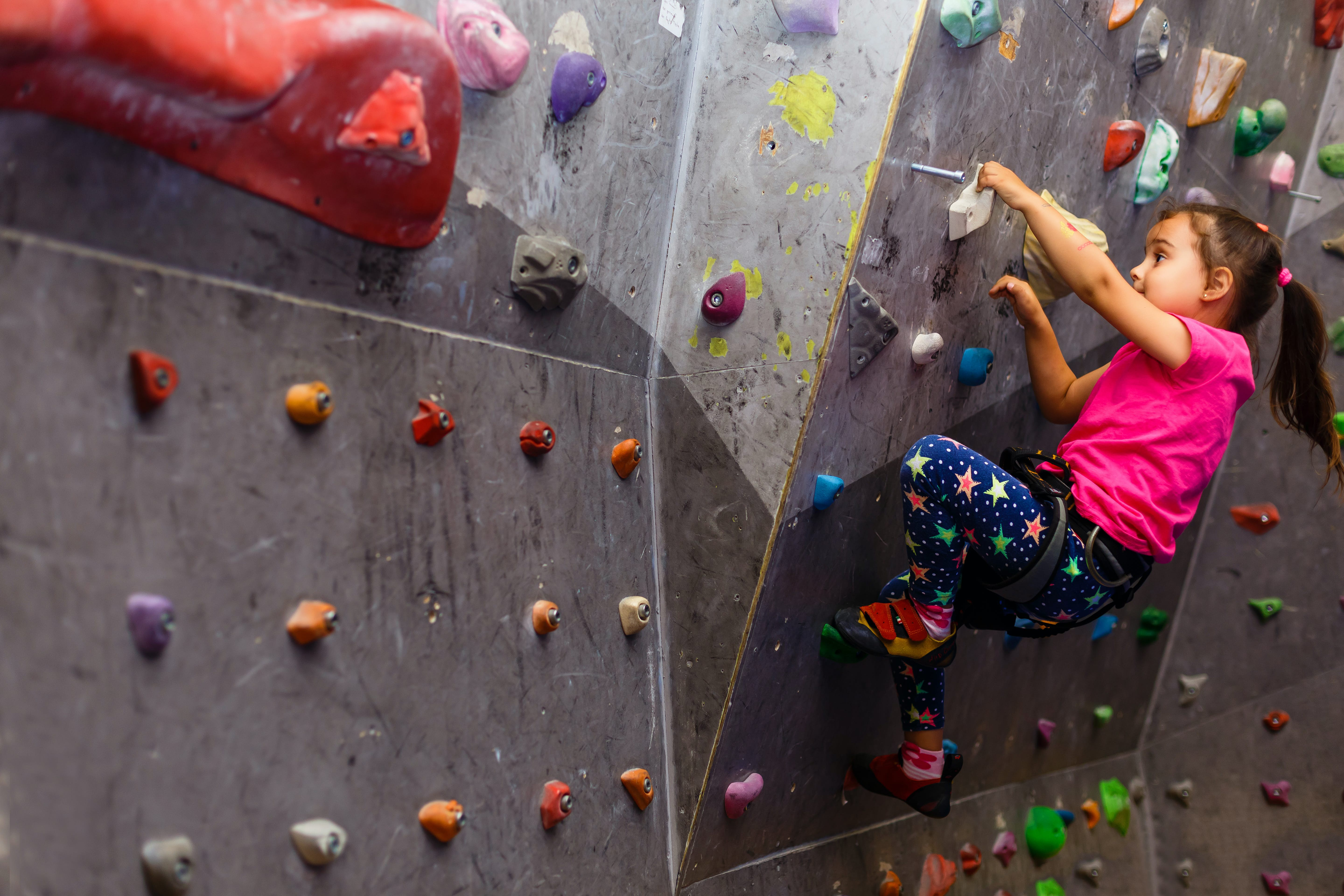 A young girl climbs on a bouldering wall in a climbing gym; kids outdoor adventures