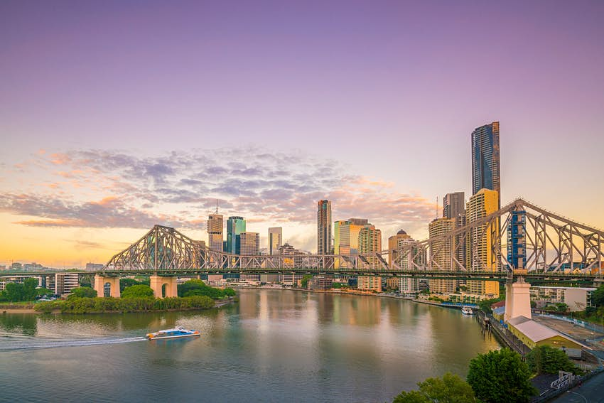 A skyline shot of Brisbane at sunset with a purple sky; the scene looks over a river and large rail bridge, with the cityscape as a backdrop.