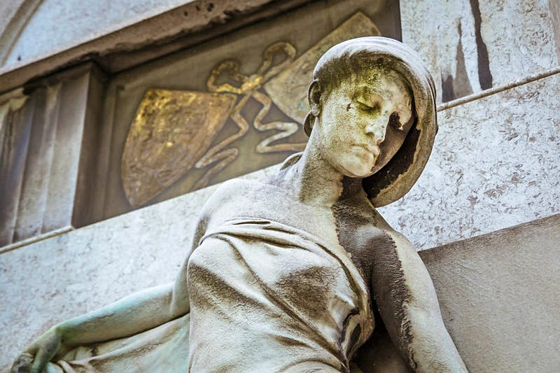 A closeup of statue of a women's face and upper body in front of a mausoleum at the Kerepesi Cemetery; Budapest autumn