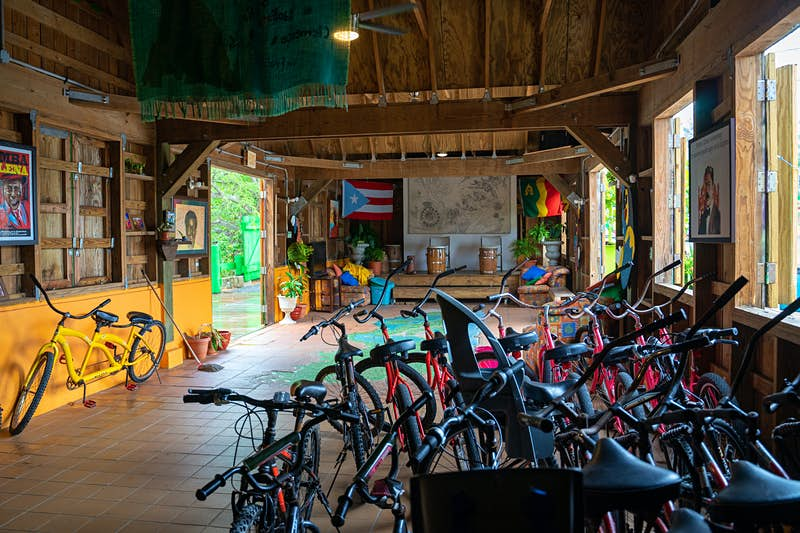 Interior of the COPI Cultural Center that houses a row of bikes towards the back of the building. The front there are two drums sitting on a stage; there is a Puerto Rico flag on the wall behind the stage; Sustainable Puerto Rico