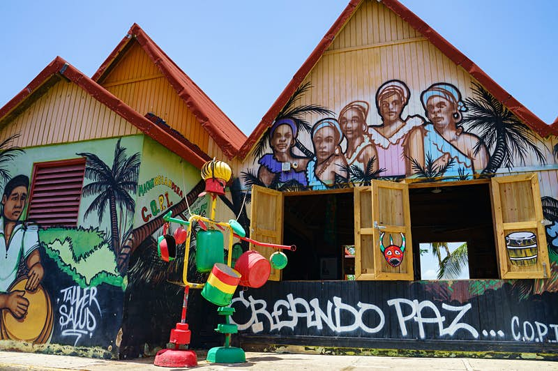 A pair of buildings are covered with images of women with head scarves and a man playing a drum; in front of the building is a colorful structure made of pots and pans; Sustainable Puerto Rico
