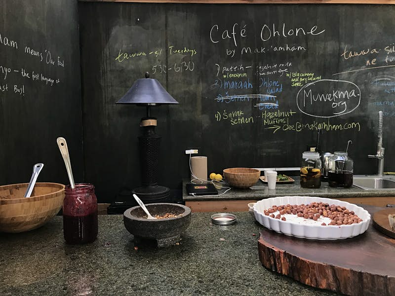 A blackboard is covered with several messages. On the front counter, there are wooden bowls, a jar of jam and mortar filled with nuts; Indigenous food