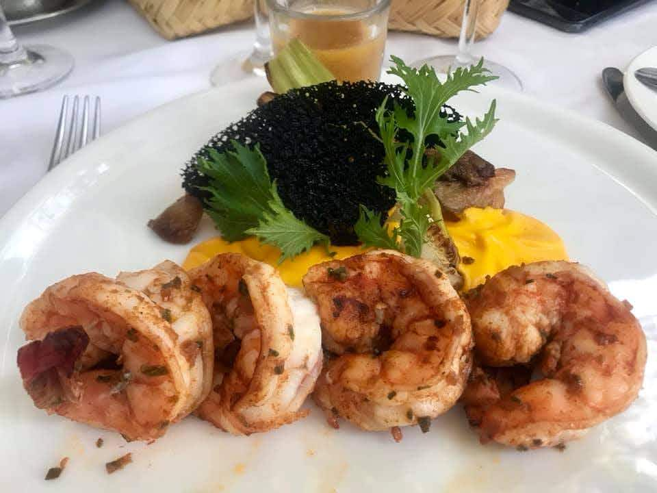 Four shrimp lay on a bed of bright yellow sauce which is topped with greenery and a black garnish