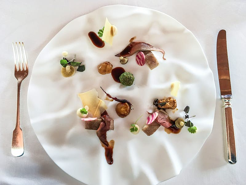 A textured white plate is filled with delicately presented morsels of food, decorated with fresh herbs.