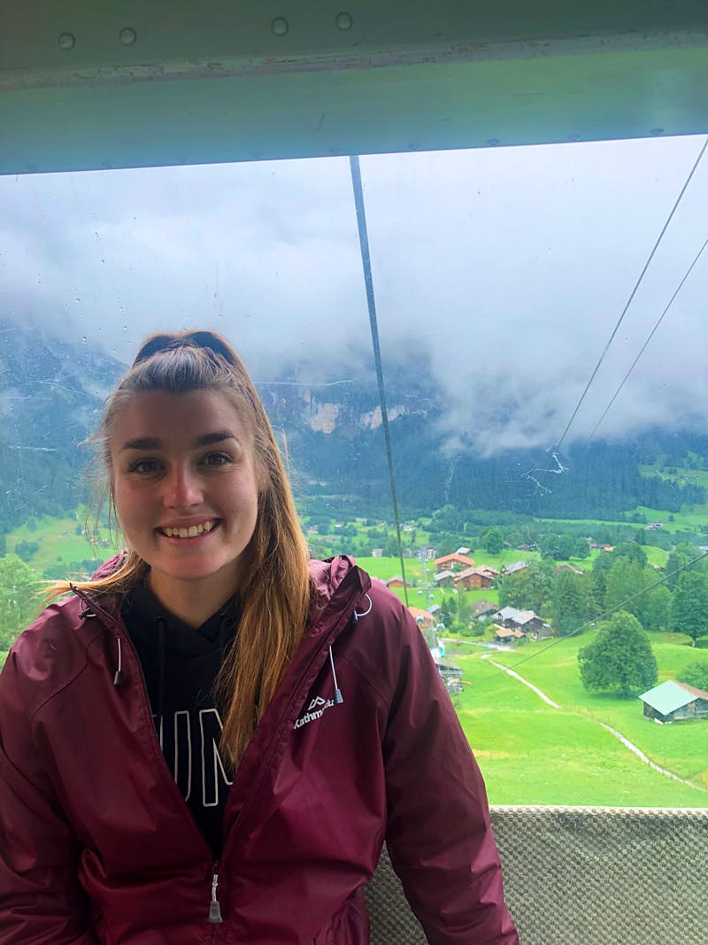 A young woman is in a cable car, riding up a mountain. She is smiling and looking at the camera and, behind her, clouds can be seen lingering above a mountain village.