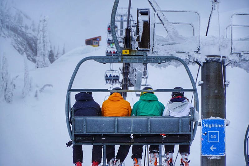 Four people in ski jackets of different colors are on a chair lift, ascending a mountain. Their backs are to the camera and it's snowing lightly.