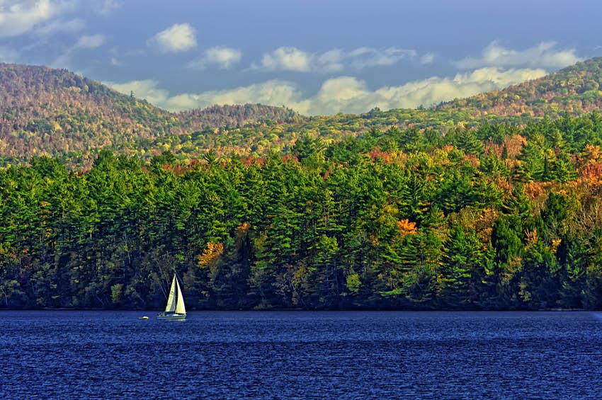 A sailboat cruises on a pristine lake as the trees on the hill behind just start to change colors; New England fall foliage road trip