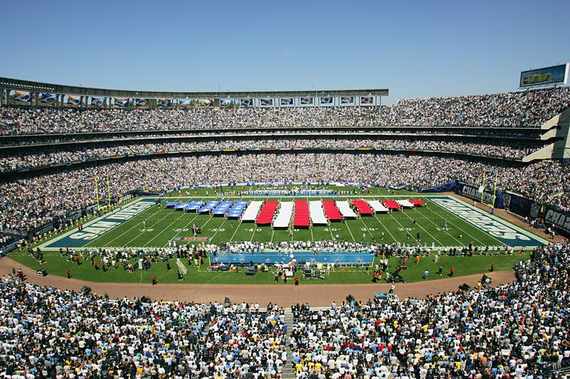 A stream making up the US flag is unfurled in the middle of the field at a packed Chargers stadium; nfl cities travel