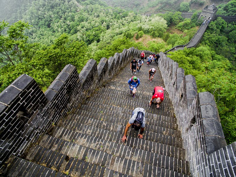 Competitors clamber up a steep section of steps on the Great Wall of China during the marathon; the wall descends behind them into the distance, with trees on each side of it.