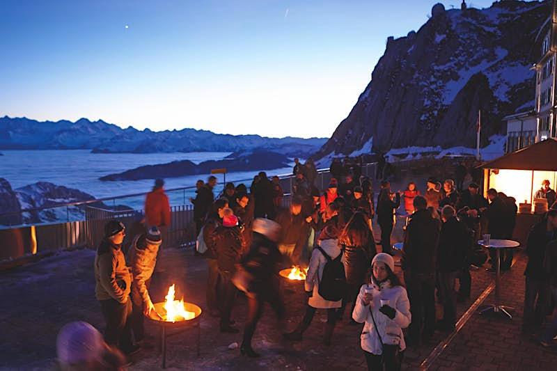People gathered on a platform on the side of a rugged, snow-covered Mt Pilatus, Switzerland. There are fires and stalls selling food and drink as part of Christkindlimärt