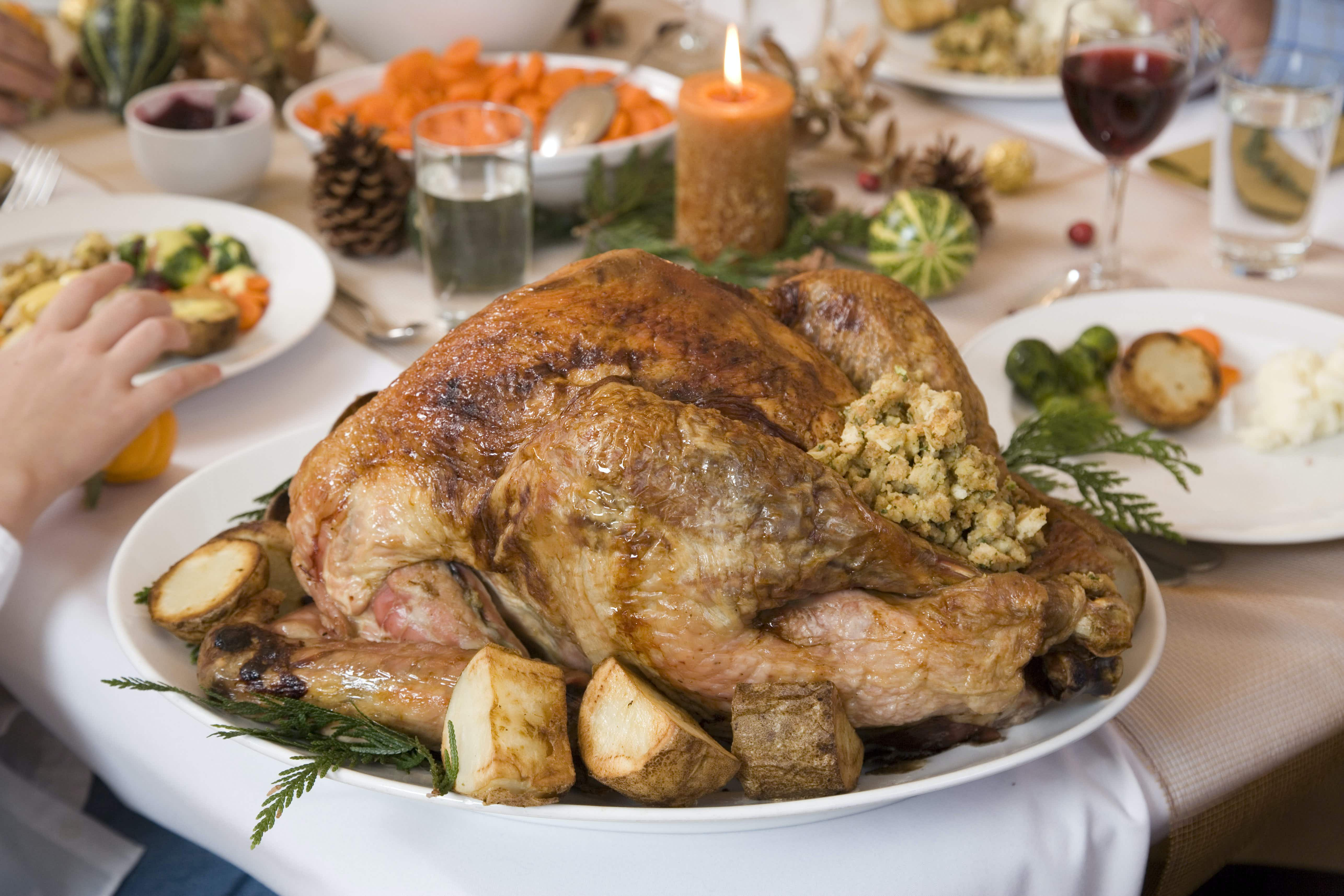 Closeup of a baked turkey filled with stuffing and surrounded by small baked potatoes. Green herbs garnish the turkey. In the background are a series of plates with food and glasses of wine and water and a large bowl of carrots.