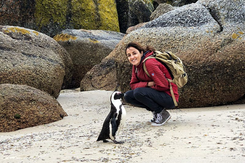 Claudia crouches down on a beach next to a penguin.
