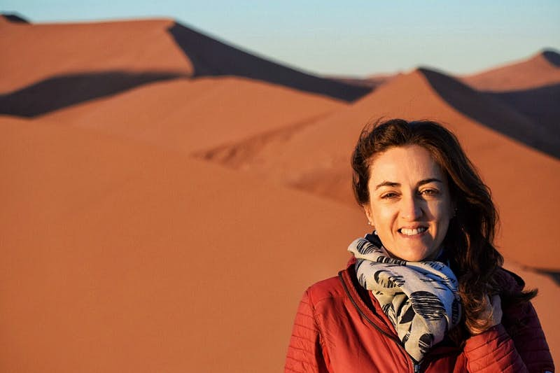Claudia poses in front of steep sand dunes in a red jacket