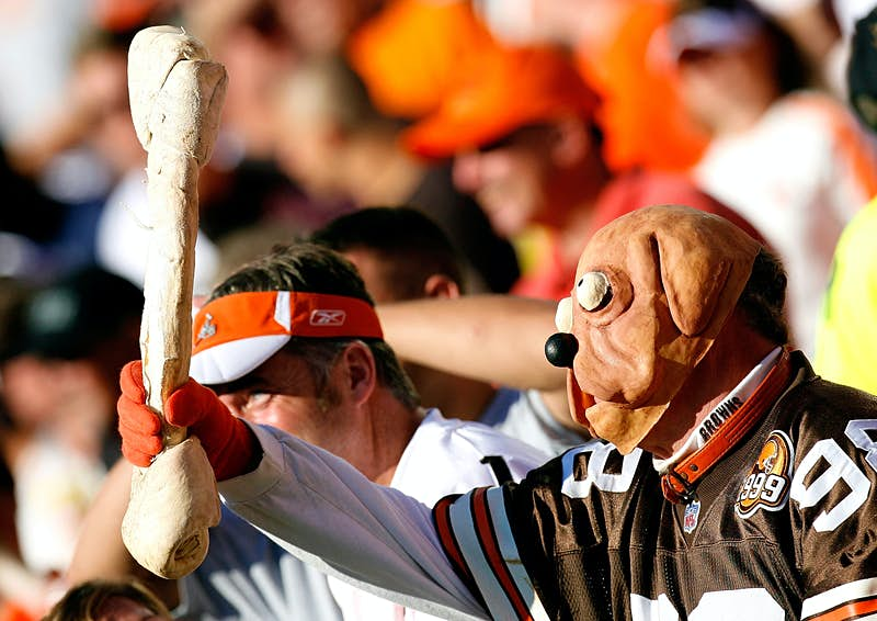 A man wears a dog mask and holds a giant dog bone during an NFL football game; nfl cities travel