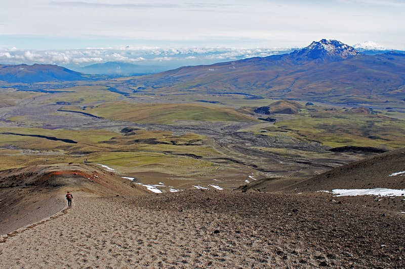 A solitary backpacker walks through scrubland on his or her way to an isolated mountain in Ecuador; Climbing a fourteener