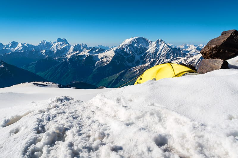 A yellow tent is partially obscured by a snow bank near the top of a very tall mountain in Russia; Climbing fourteeners for beginners