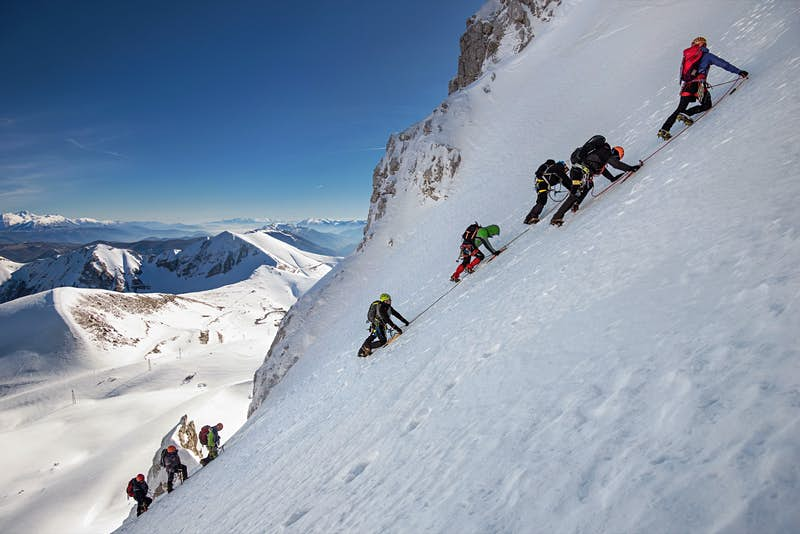 A line of ice climbers ascends a steep snow-covered peak in France; Climbing fourteeners for beginners