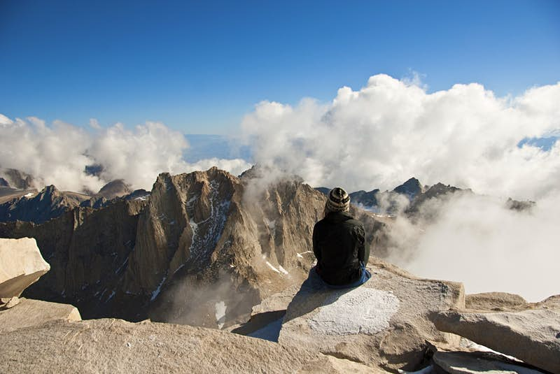A woman sits at the summit of a mountain looking down at the clouds mixing around the surrounding peaks; Mountain climbing fourteeners