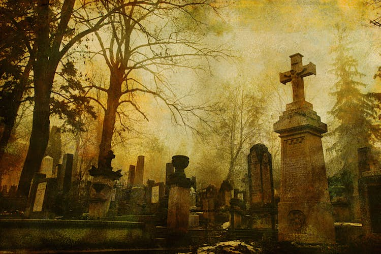 A sepia-toned photo of old cemetery grave stones and bare tree branches; haunted places world