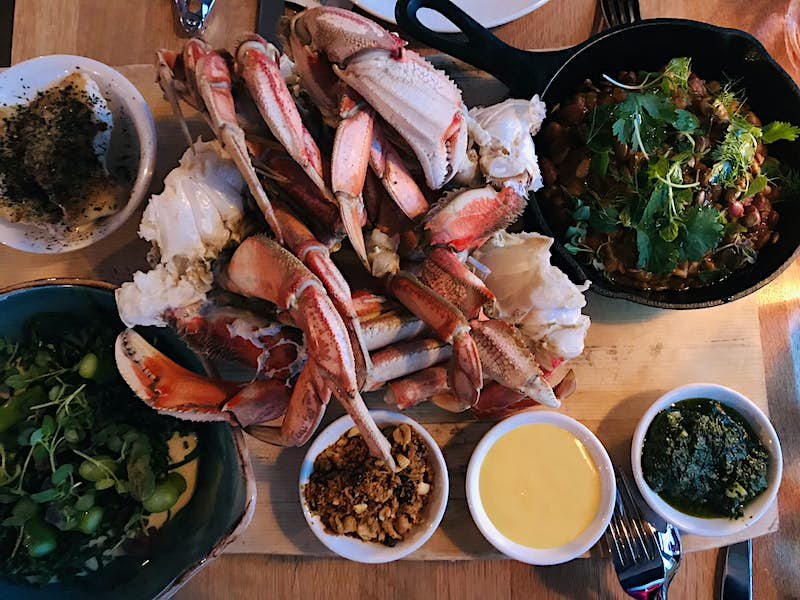 A blonde wooden table is laden with dishes at 1909 Kitchen. In the center is a huge pile of pink and white crab legs. To the lower left is a deep blue bowl with foraged micro-greens. Three small bowls are filled with peanuts and sauces. A small cast iron skillet in the top right is full of a brown dish garnished with parsley and more bright greens.