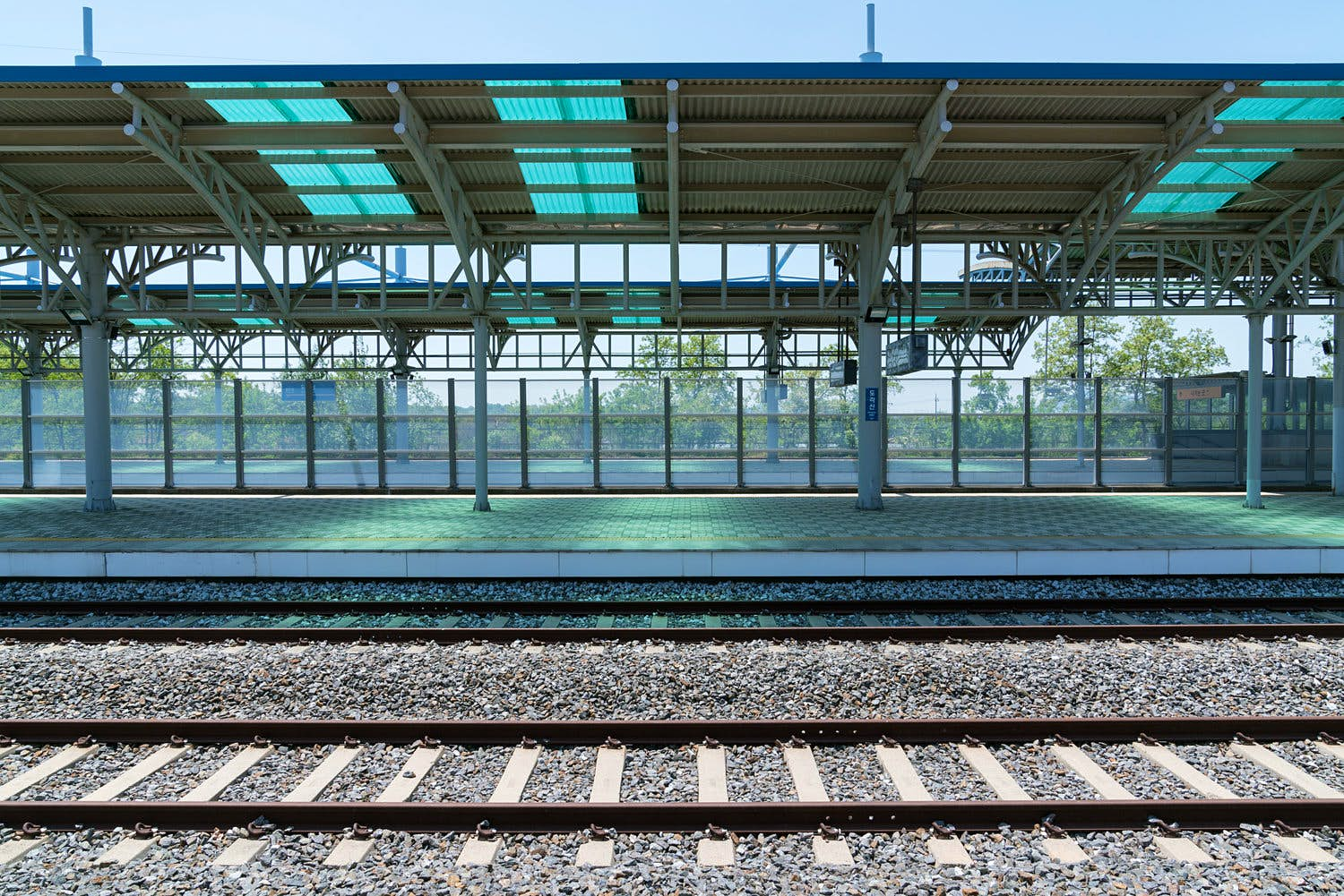 An empty platform at the abandoned Dorasan Station, in Korea. Glass paneling separates the platform from woodland outside, while a track is visible in front.