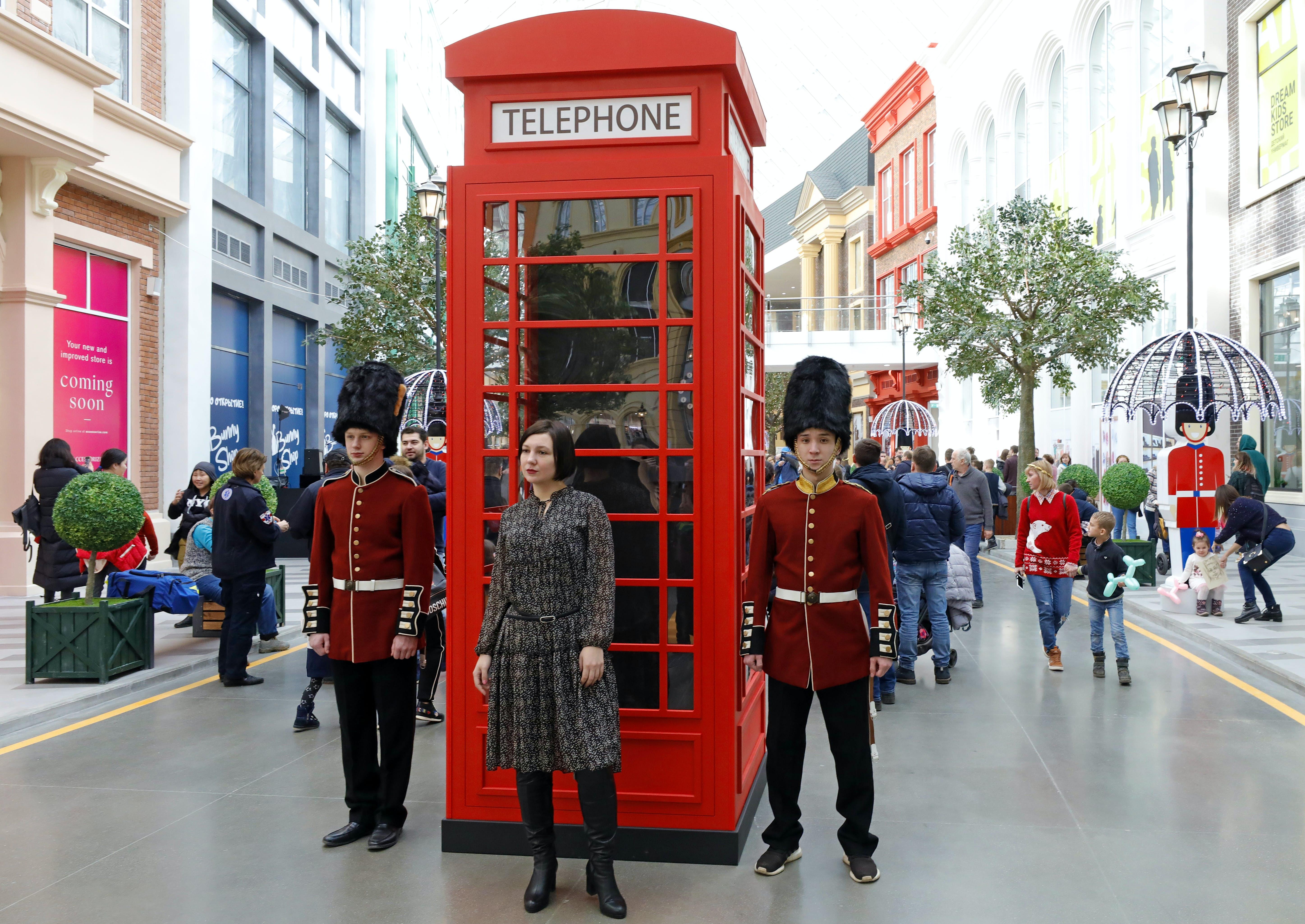 Uma caixa telefônica tradicional de Londres e guardas reais em um parque temático coberto