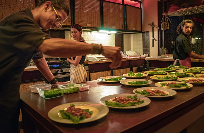 A chef sprinkles garnish over a plate of food as a pair of other chefs look on. The table is filled with dishes filled with food in a kitchen; Sustainable Puerto Rico