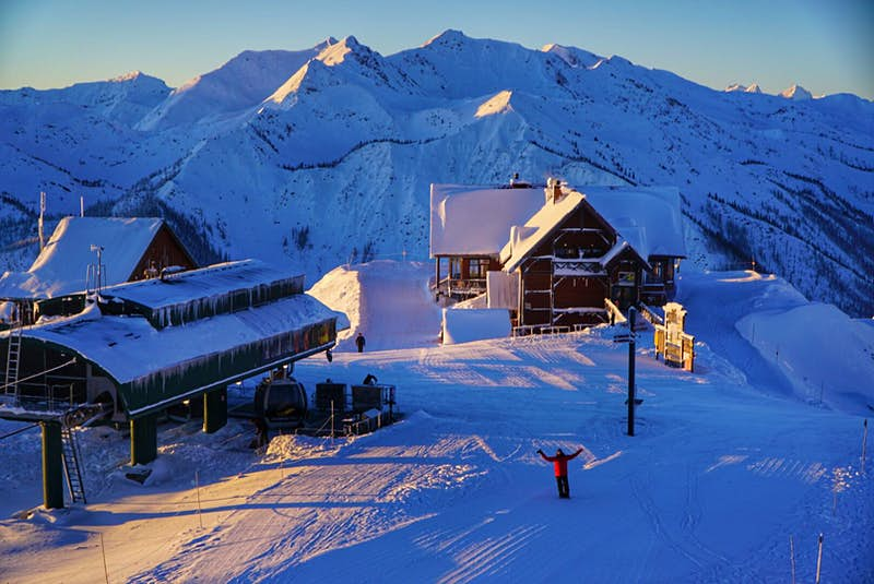 A person in a red ski jacket and black pants is joyfully holding up their arms; they're standing at the top of a piste, beside a ski-lift station. Behind them is a mountain chalet and, beyond that, are mountains covered in snow.