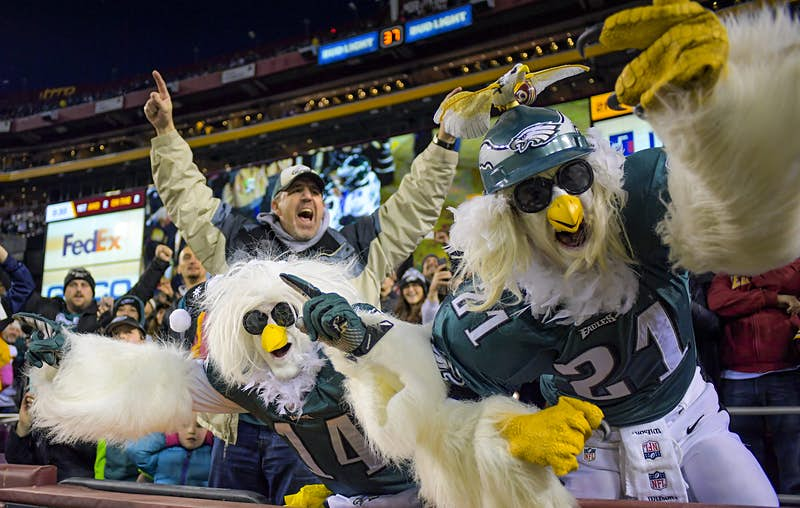 A pair of people dressed up as eagles stand up and cheering during and NFL game between the Philadelphia Eagles and Washington Redskins; nfl cities travel