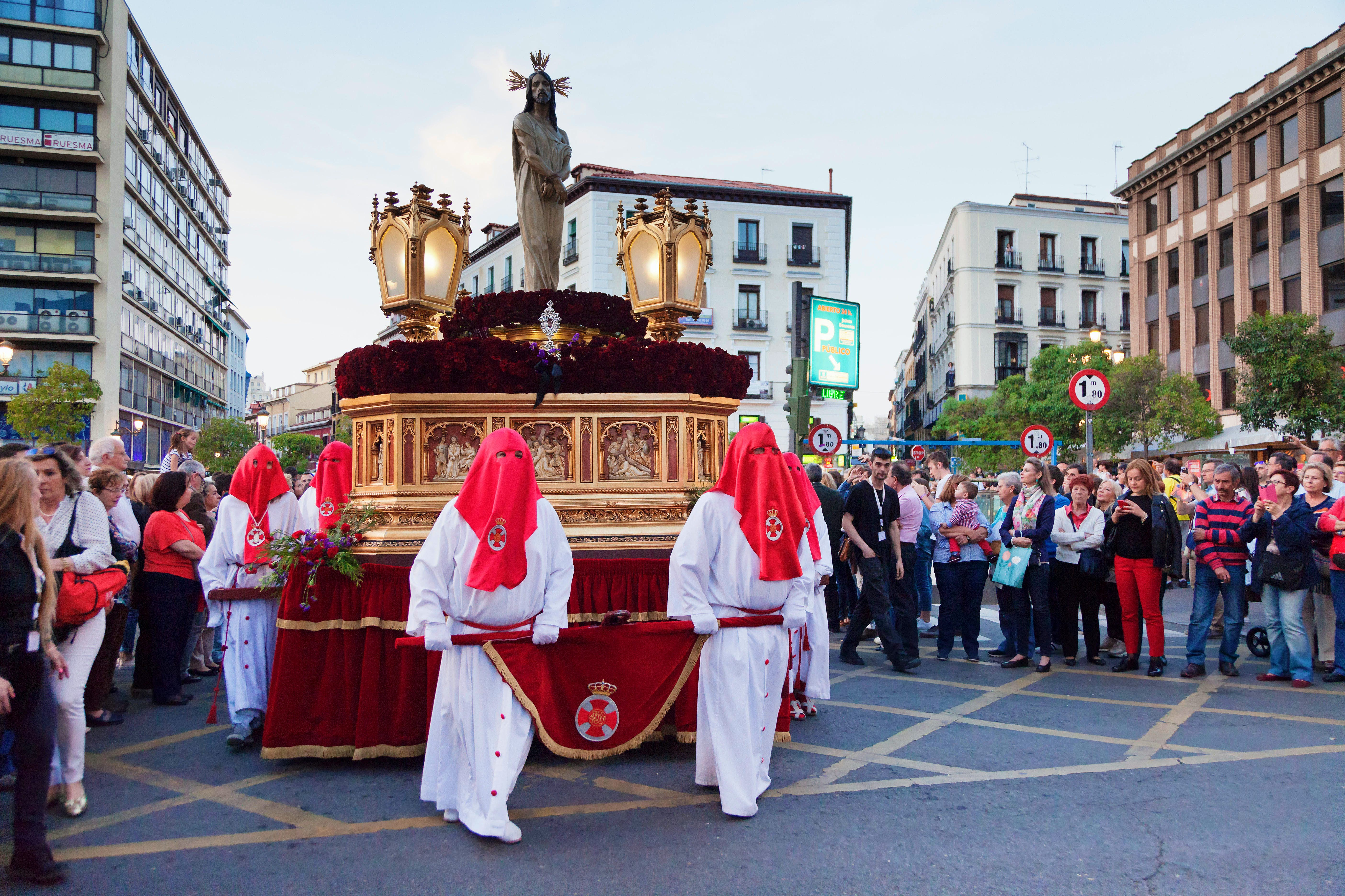 People parading through the streets dressed in white robes with red hoods covering their faces during Semana Santa in Madrid, Spain.