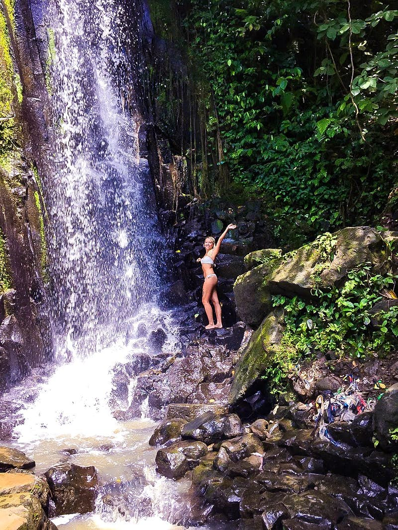 Fabiana stands beneath a waterfall in a white swimsuit.