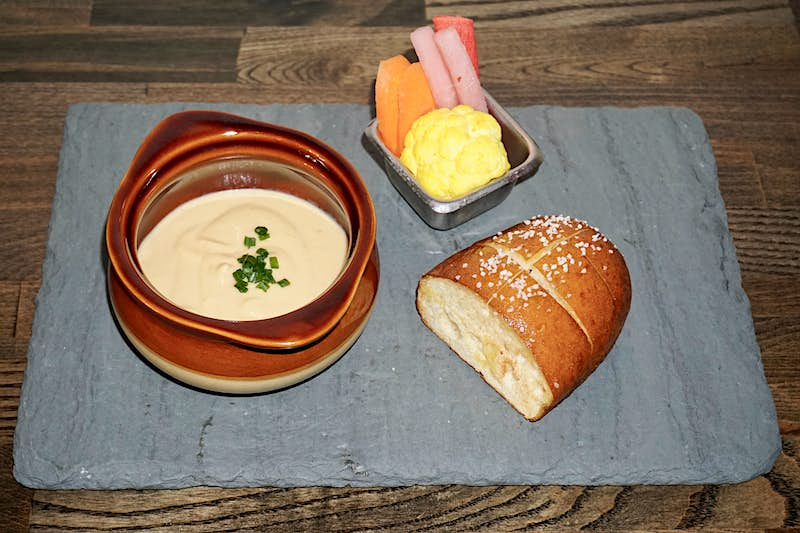 A gray slate, being used as a plate, sits on a dark wooden table; on the slate is a chunk of golden brown bread, a metal ramekin filled with crudités, and an earthenware bowl filled with molten vegan cheese, garnished with green herbs.