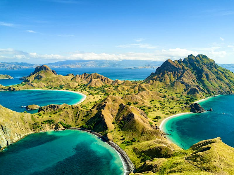 Aerial of the mountainous Pulau Padar island, Indonesia. Taken on a sunny day with a few fluffy clouds in the far distance, the verdant green hills contrast against the deep, jewel-blue sea.